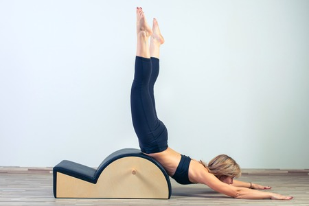 Pilates, fitness, sport, training and people concept -  woman doing  exercises on small barrel. Фото со стока