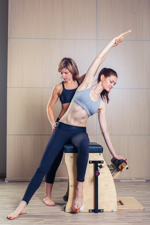 pilates woman: combo wunda pilates chair woman with instructor fitness yoga gym exercise