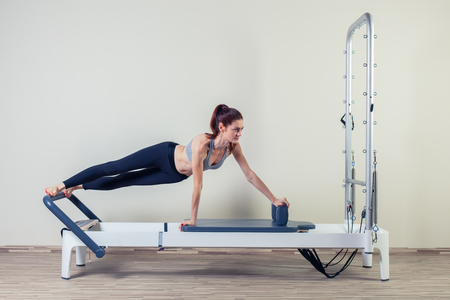 exercise machine: Pilates reformer workout exercises woman brunette at gym indoor. Stock Photo