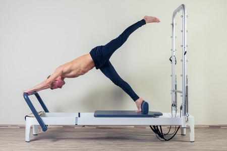 reformer: Pilates reformer workout exercises man  at gym indoor. Stock Photo