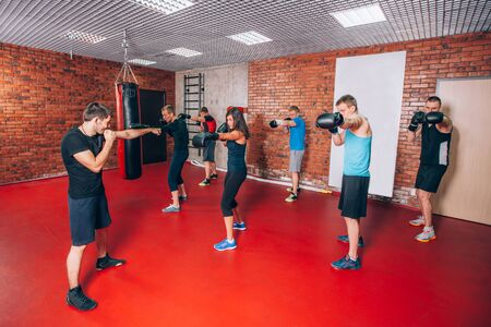 adult sexual: Boxing aerobox group with personal trainer man at fitness gym, gloves, punching bag.