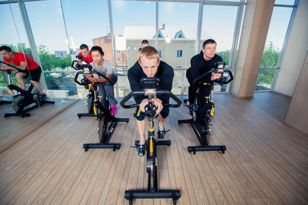Group of gym people on machines, cycling In Class.