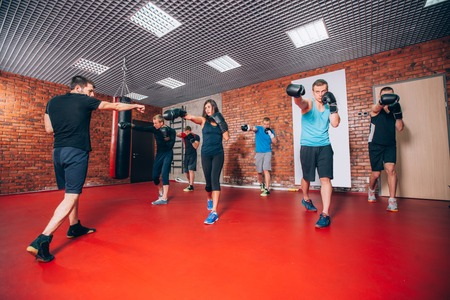 girl punch: Boxing aerobox group with personal trainer man at fitness gym, gloves, punching bag.