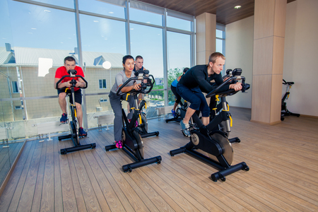 machines: Group of gym people on machines, cycling In Class.