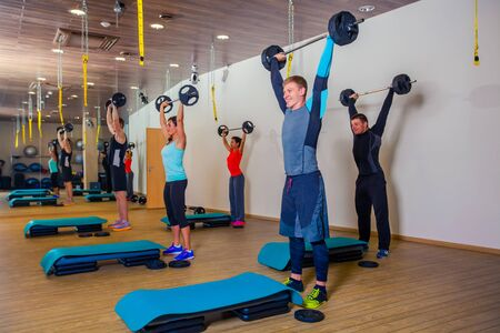 barbell: Sport, fitness, lifestyle and people concept - group flexing muscles with barbells in gym. Stock Photo