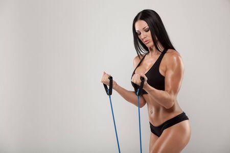 silhouette feminine: Sportive exercice avec une bande de r�sistance sur fond gris. Banque d'images