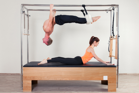 aerobic instructor: Pilates aerobic instructor woman and man  in cadillac fitness exercise.