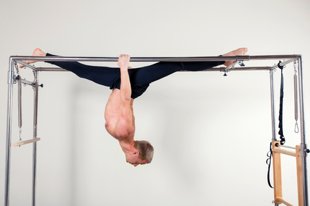 aerobic instructor: Pilates aerobic instructor man in cadillac fitness exercise. acrobatic upside down balance
