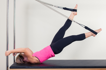 aerobic instructor: Pilates aerobic instructor woman in cadillac fitness exercise.