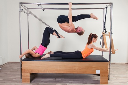 aerobic instructor: Pilates aerobic instructor a group of three people in cadillac fitness exercise. Stock Photo
