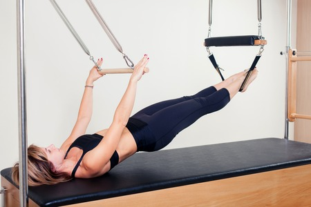 aerobics: Pilates aerobic instructor woman in cadillac fitness exercise.