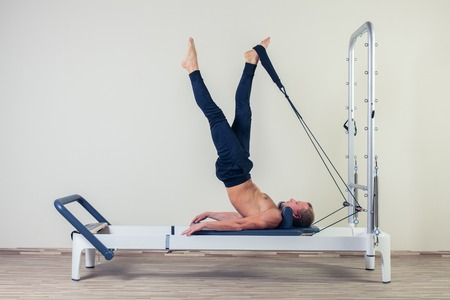 Pilates reformer workout exercises man  at gym indoor. Stock fotó