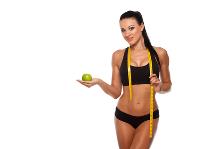 loss weight: Sporty woman waist with measure tape and green apple isolated on white.