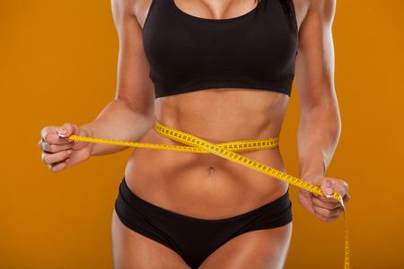 cinta de medir: Deporte, fitness y dieta concepto - cerca de vientre entrenado con cinta métrica. Foto de archivo