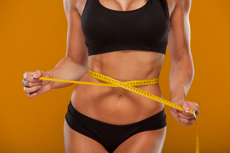 Sport, fitness and diet concept - close up of trained belly with measuring tape. Stock Photo