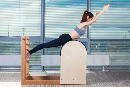 laying abs exercise: Pilates, fitness, sport, training and people concept - smiling woman doing  exercises on ladder barrel.