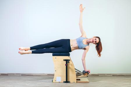 reformer: combo wunda pilates chair woman fitness yoga gym exercise. Stock Photo