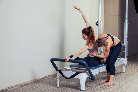 Pilates reformer workout exercises man with instructor  at gym indoor, Stock fotó
