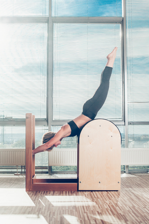 Pilates, fitness, sport, training and people concept - smiling woman doing  exercises on ladder barrel.