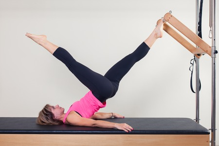 gimnasia aerobica: Pilates instructor de la mujer en el ejercicio de la aptitud aeróbica cadillac.
