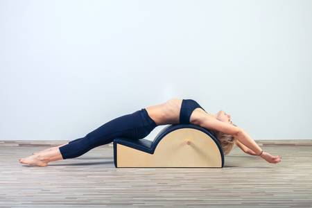Pilates, fitness, sport, training and people concept -  woman doing  exercises on small barrel. Standard-Bild