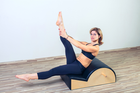 personal goals: Pilates, fitness, sport, training and people concept -  woman doing  exercises on small barrel. Stock Photo