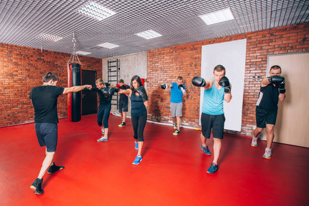 sexual background: Boxing aerobox group with personal trainer man at fitness gym, gloves, punching bag.
