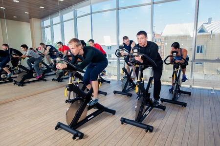 group fitness: Group of gym people on machines, cycling In Class.