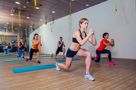 lifting: People at the health club with personal trainer, learning the correct form. Stock Photo