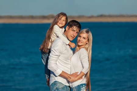 adult couple: Young family in blue jeans hugging on the background of water.