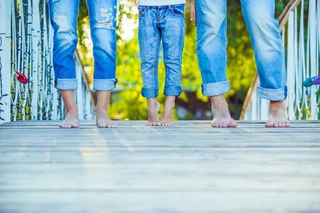 ragazze a piedi nudi: Famiglia felice su una camminata in estate. Bambino con i genitori insieme. Piedi a piedi nudi. Stile di vita sano. Papà Mamma e figlio. Primavera. Archivio Fotografico