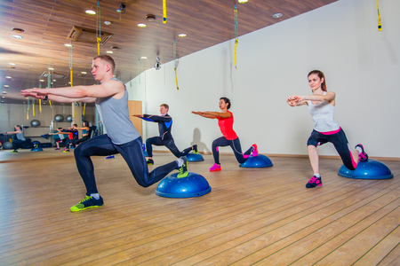 People at the health club with personal trainer, learning the correct form. Fitness group training with bosu at the gym.