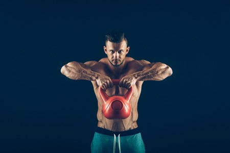 Fitness man doing a weight training by lifting a heavy kettlebell. Stock fotó