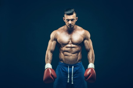 Muscular boxer in studio shooting, on black background