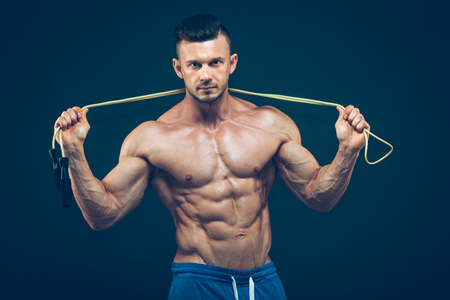 abs: Muscular man skipping rope. Portrait of muscular young man exercising with jumping rope on black background. Stock Photo
