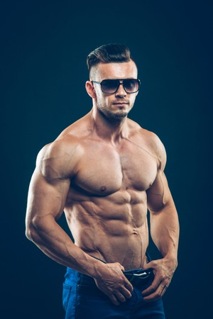 strong athletic man  in sunglasses on black background. To pump the abdominals.