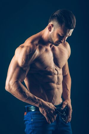 strong athletic man   on black background. To pump the abdominals.