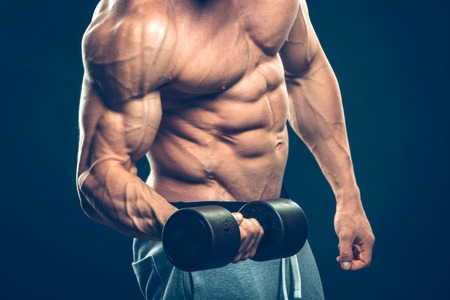 human arm: Closeup of a muscular young man lifting dumbbells weights on dark background . Stock Photo