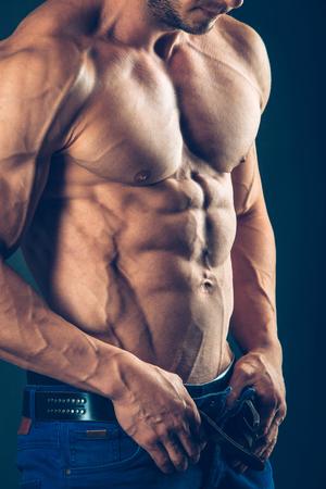 atletismo: hombre atlético fuerte en fondo negro. Para bombear los abdominales. Foto de archivo