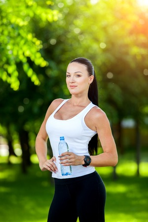 day break: woman athlete takes a break, she drinking water, out on a run on a hot day