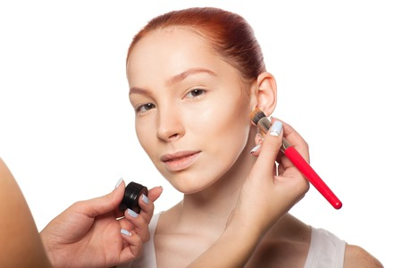 fair skin: Professional Make-up artist doing glamour with red hair model makeup. Beautiful woman face. Perfect makeup. In Set -makeup 01-  all stages of makeup. Isolated background. Stock Photo