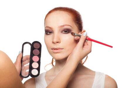 fair complexion: Professional Make-up artist doing glamour with red hair model makeup. Beautiful woman face. Perfect makeup. In Set -makeup 01-  all stages of makeup. Isolated background. Stock Photo