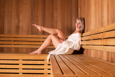 sauna nackt: Beautiful woman sitting relaxed in a wooden sauna white coat.