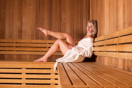 Schöne Frau sitzt in einer hölzernen Sauna weißen Mantel entspannt.