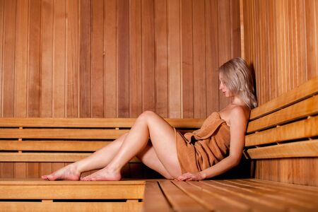 sweat girl: Beautiful woman sitting relaxed in a wooden sauna in a brown towel. Stock Photo