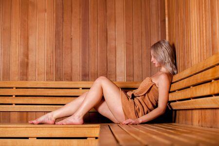 toallas: Mujer hermosa sentada relajada en una sauna de madera en una toalla de color marrón.
