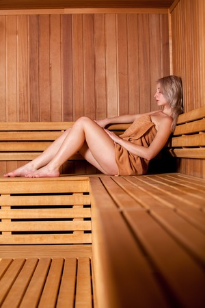 nude body: Beautiful woman sitting relaxed in a wooden sauna in a brown towel. Stock Photo
