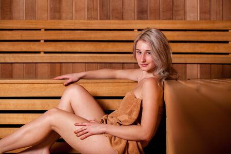 finnish bath: Beautiful woman sitting relaxed in a wooden sauna in a brown towel. Stock Photo