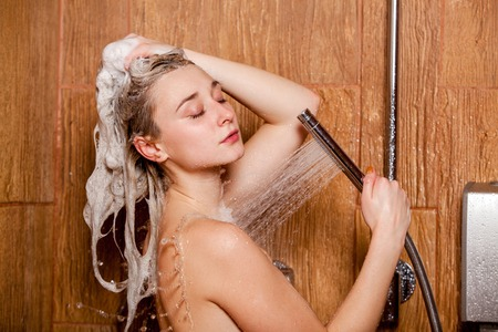 female in douche: Beautiful woman standing at the shower.  She holds in her hand showerhead.