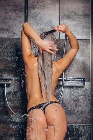 female in douche: beautiful woman standing at the shower. Woman is washing her hair.
